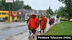 A group of local Laotian and Buddhist monks from Wat Lao Samakky Temple walk with Phra Sutham Nateetong, the Thai monk who is walking for peace across America, Fort Wayne, Indiana June 9, 2019.