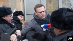FILE - Russian opposition leader Alexei Navalny, center, is detained by police officers in Moscow, Jan. 28, 2018.