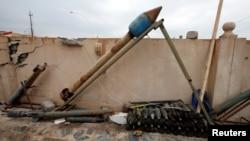 FILE - Weapons and ammunition belonging to Islamic State militants are seen in the town of Bashiqa, east of Mosul, Iraq.