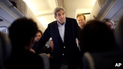 Menteri Luar Negeri AS John Kerry berbicara dengan wartawan di pesawat sebelum pergi ke Wina, Austria, di pangkalan udara Andrews di Maryland (26/6).