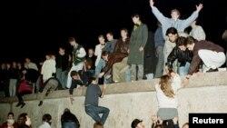 Фото з архіву: жителі східного Берліна перелізають через Берлінську стіну, святкуючи відкриття кордону між східною і західною частинами міста. 10 листопада 1989 р.