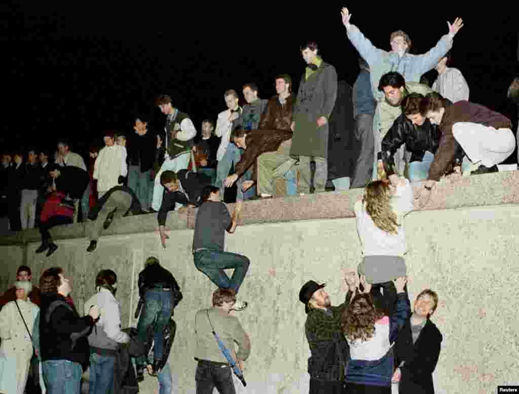 با بازشدن بخشی از دیوار برلین، شهروندان آلمان شرقی در دروازه برندنبرگ خود را به بالای دیوار رساندهاند – ۱۹ آبان ۱۳۶۸