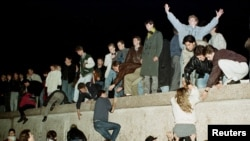 FILE - East German citizens climb the Berlin Wall at the Brandenburg Gate in November 1989 as they celebrate the opening of the East German border