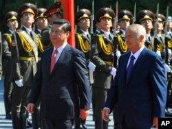 习近平今年9月访问乌兹别克斯坦时和东道国总统卡里莫夫在欢迎仪式上。