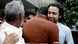 People comfort Musa Gilani, right, the brother of Ali Haider Gilani who has been kidnapped in Multan, Pakistan, May 9, 2013.