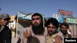 在巴基斯坦西南部的警察训练中心遭到攻击后,警察亲属们在门口焦急的等待(2016年10月25日)
