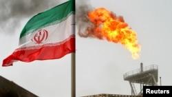 Un drapeau iranien vole au dessus d'une production de pétrole, en Iran, le 25 juillet 2005.