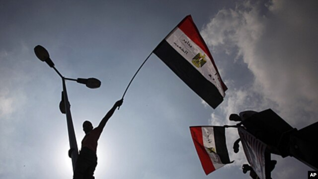Egyptian protesters wave from lamp posts hanging their national flags at Tahrir Square, the focal point of the Egyptian uprising, in Cairo, September 9, 2011.