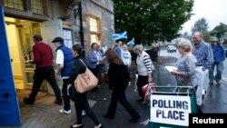 Para peseta pemilu memasuki sebuah TPS untuk memberikan suara mereka dalam referendum kemerdekaan Skotlandia di Pitlochry, Skotlandia (18/9).