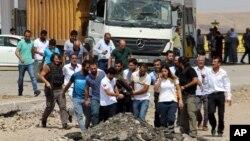 Các nhân viên y tế và người dân khiêng những thi thể đi sau một vụ nổ ở sở cảnh sát gần thành phố Diyarbakir, phía đông nam Thổ Nhĩ Kỳ, ngày 15 tháng 8 năm 2016.
