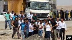2016年8月15日人们在土耳其东南的吉兹瑞市警察哨所发生汽车炸弹爆炸后抬着一具尸体。