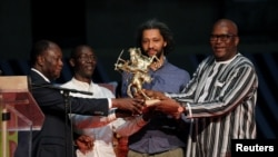 "The French-Senegalese Alain Gomis (2nd R), director of the movie ""Felicite,"" receives the Etalon d'Or de Yennenga from Burkina Faso's President Roch Marc Christian Kabore (R) and Ivory Coast's president Alassane Ouattara (L) during the FESPACO film festival, March 4, 2017."