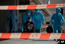 A resident of The Salvation Army Lung Hang Residence for Senior Citizens is evacuated by medical staff from the Centre for Health Protection, after employees of the nursing home were found to have the coronavirus, in Hong Kong.