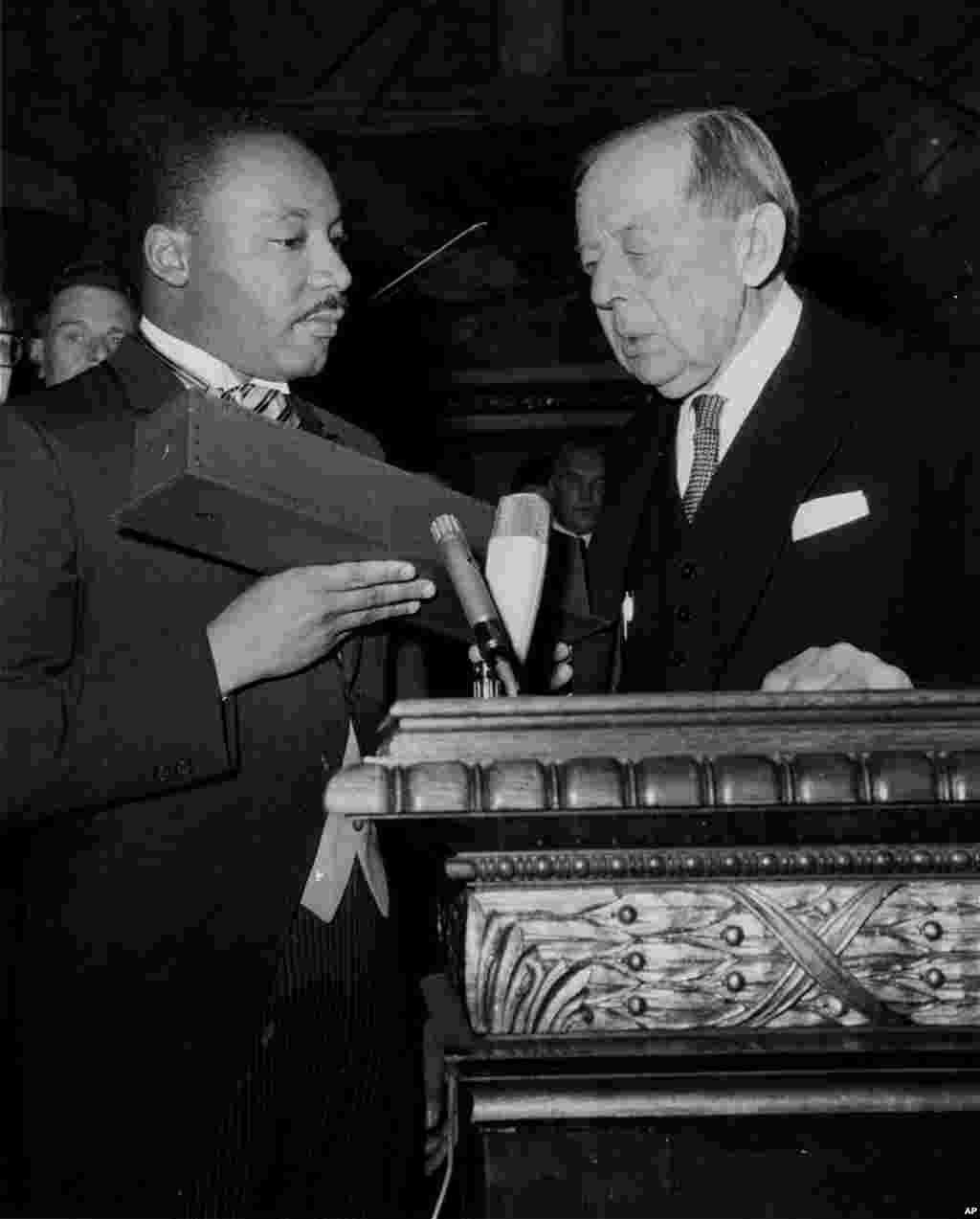 លោក Martin Luther King, Jr. កាន់ប្រអប់មួយដែលមានមេដាយមាសនៃពានរង្វាន់ណូបែលសន្តិភាព បន្ទាប់ពីពេលដែលលោកទទួលបាននៅក្នុងក្រុងអូស្លូ (Oslo) ប្រទេសន័រវែស កាលពីថ្ងៃទី១០ ខែធ្នូ ឆ្នាំ១៩៦៤។