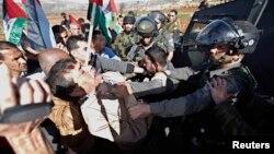 Член кабинета министров Палестинской автономии Зиад Абу Эйн участвует в потасовке с военным полицейским из пограничной службы Израиля недалеко от города Рамалла. 10 декабря 2014 г.