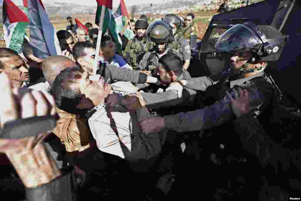 Palestinian minister Ziad Abu Ein (L) scuffles with an Israeli border policeman near the West Bank city of Ramallah. Abu Ein died shortly after being hit by Israeli soldiers during a protest in the occupied West Bank, a Reuters photographer who witnessed the incident and a Palestinian medic said.