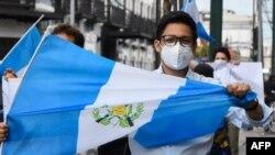 Un hombre sostiene una bandera guatemalteca durante una demostración para exigir al gobierno que ponga fin a las medidas de confinamiento. Mayo 2020.