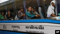 FILE PHOTO - Cambodian migrant workers sit in a bus upon arrival at Cambodia-Thailand's international border gate in Poipet, Cambodia, from Thailand, Tuesday, June 17, 2014.