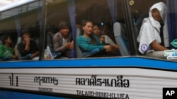 FILE - Cambodian migrant workers sit in a bus upon arrival at Cambodia-Thailand's international border gate in Poipet, Cambodia, from Thailand, Tuesday, June 17, 2014.