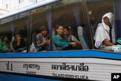 FILE: Cambodian migrant workers sit in a bus upon arrival at Cambodia-Thailand's international border gate in Poipet, Cambodia, from Thailand, Tuesday, June 17, 2014.