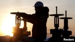 FILE - A worker checks the valve of an oil pipe at the Lukoil owned Imilorskoye oil field near Kogalym, Russia, Jan. 25, 2016.