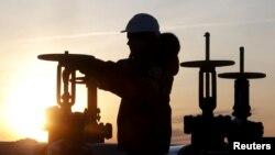 Seorang pekerja memeriksa pipa minyak di Lapangan Imilorskoye milik Lukoil, dekat Kogalym, Rusia, 25 Januari 2016.