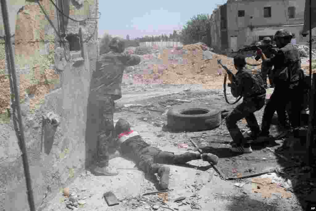 Syrian army personnel shoot towards rebel fighters during a tour for journalists organized by the Syrian Information Ministry in the Damascus suburb of Jobar, July 14, 2013.
