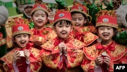 Children wearing traditional costumes pose during preparations for Chinese lunar new year celebrations in Hong Kong on February 17, 2015.