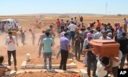 In this image made from video, mourners carry a coffin during the burial of Rehan Kurdi and her sons Alan, 3, and Galip, 5, after they drowned during a desperate voyage from Turkey to Greece, in their hometown of Kobani, the Syrian Kurdish region they fl