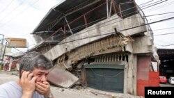 Un residente pasa frente a una casa colapsada durante un terremoto en la ciudad de Cebu, en el centro de las Filipinas.