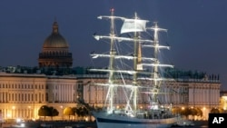 The Russian tall ship Mir (Peace) sails along the Neva River with the Hermitage (Winter Palace) in the background.