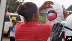 Un travailleur sanitaire aidant un collègue avec son équipement de protection pour recueillir le corps d'un homme soupçonné d'avoir succombé au virus d'Ebola à Monrovia, au Libéria, le 12 août 2014.