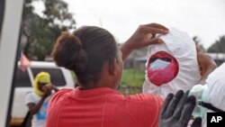 Petugas kesehatan mengenakan pakaian pelindung sebelum memindahkan jenazah pasien Ebola yang tewas di Monrovia, Liberia (12/8).