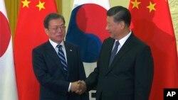 资料照片:中国国家主席习近平在北京人大会堂会见到访的韩国总统文在寅。(2019年12月23日)