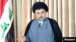 FILE- Iraqi Shi'ite cleric Moqtada al-Sadr gives a speech in Najaf, Iraq, June 25, 2014. Al-Sadr has emerged as a leading figure behind the recent anti-government protests in Baghdad.