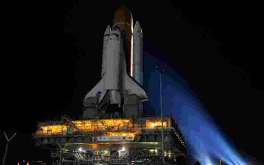 """En medio de luces de xenón brillante, el transbordador Discovery hace su caminata nocturna, conocida como """"lanzamiento"""" al Edificio de Ensamblaje de Vehículos a plataforma de lanzamiento de la NASA."""