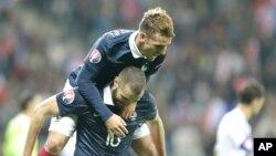 Antoine Grieazamnn de la France grimpe sur le dos de son co-équipier Karim Benzema après le but de ce dernier lors du match amical contre l'Argentine à Nice, France, 8 octobre 2015.