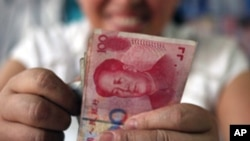 FILE - A bookstore vendor counts Chinese renminbi notes in Chengdu, in southwest China's Sichuan province.