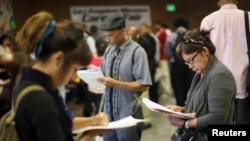 FILE - Job seekers fill out applications in Los Angeles, California, May 31, 2012.