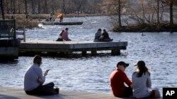 Para pengunjung taman Charles River Esplanade di Boston duduk-duduk menikmati cuaca hangat yang tak biasanya, 12 Januari 2020. (Foto: AP)