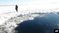 Miệng hố hình tròn trên lớp băng của Hồ Chebarkul nơi tin tức nói là mảnh vỡ của thiên thạch đã rớt xuống gần Chelyabinsk, cách Moscow khoảng 1500 kilomét về hướng đông, ngày 15/2/2013.