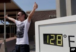 Cheng Jia, of China, poses by a digital thermometer at the Furnace Creek Vistitor Center in Death Vally National Park