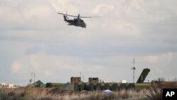 Một máy bay trực thăng của Nga tuần tra trong khi các hệ thống tên lửa phòng không được nhìn thấy ở bên dưới tại căn cứ không quân Hemeimeem ở Syria, ngày 20 tháng 1 năm 2016.