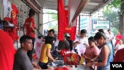 缅甸仰光民盟总部门外,民盟的拥护者们正在抢购印有昂山素季及民盟旗帜的纪念品。(美国之音朱诺拍摄)