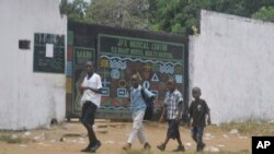 Children walk past JFK Medical centre in Monrovia, Liberia. Ebola centers. The trauma of the world's deadliest Ebola outbreak, which killed more than 11,300, has left many survivors fighting a mental health battle to focus on the present, after witnessing drawn-out deaths and whole communities torn apart, March. 31, 2017.