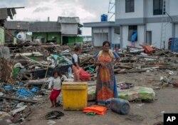Las personas buscan en los escombros cerca de los sitios donde estaban sus casas antes del devastador tsunami en Indonesia.