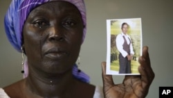 Martha Mark, the mother of kidnapped school girl Monica, cries as she displays her photo, in the family house, in Chibok, Nigeria, in this file photo from May 19, 2014.