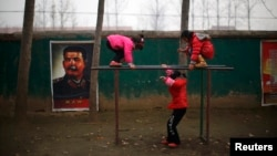 Students play next to a portrait of Soviet leader Joseph Stalin at the Democracy Elementary and Middle School in Sitong town, Henan province, China, Dec. 3, 2013.