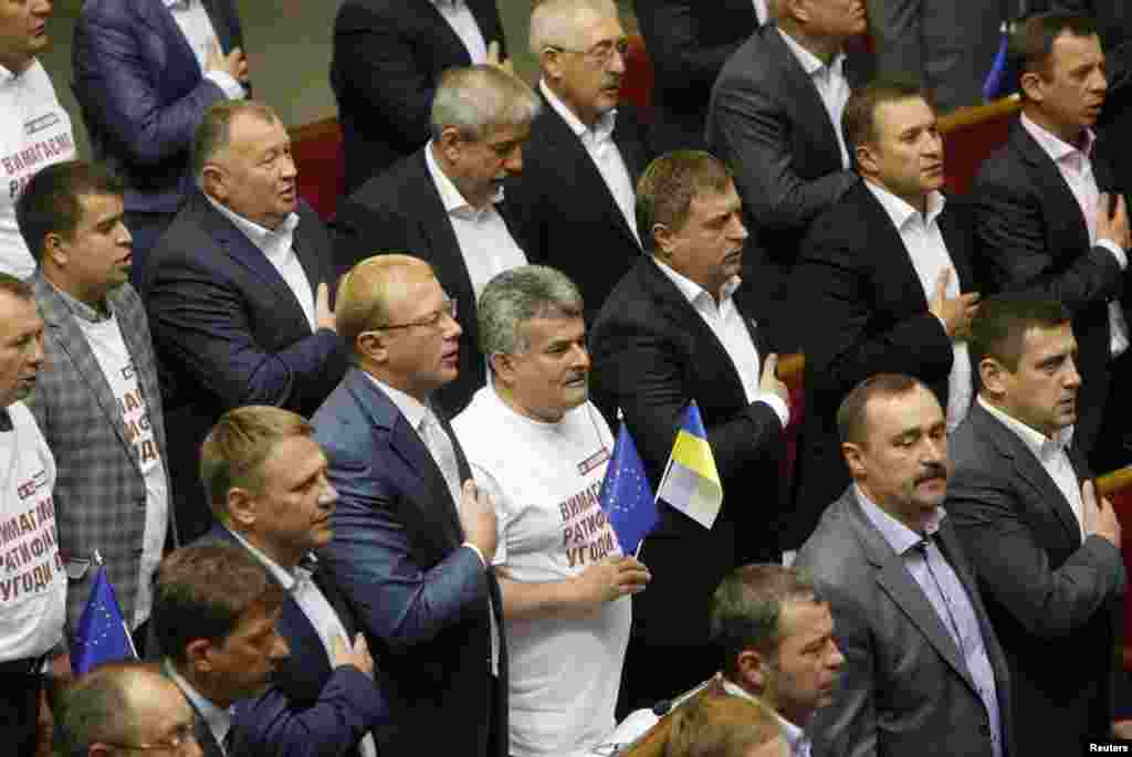 Ukrainian lawmakers sing the national anthem after ratifying a landmark association agreement with the European Union during a parliament session in Kyiv Sept. 16, 2014.