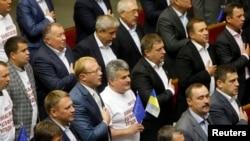 Para anggota parlemen Ukraina menyanyikan lagu kebangsaan setelah meratifikasi kesepakatan untuk memperluas hubungan ekonomi dan politik dengan Uni Eropa di Kyiv (16/9).